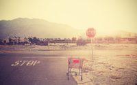 Einkaufswagen steht verlassen an einer Straße mit Stoppschild