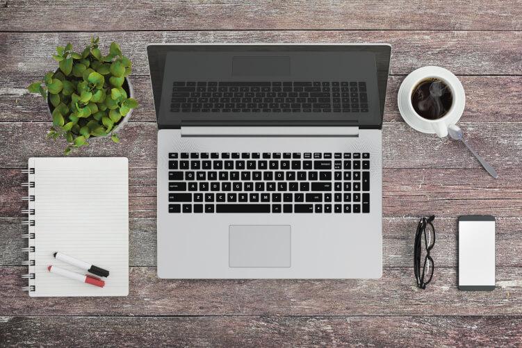 Laptop, Kaffee und Block in einer Content-Marketing-Agentur