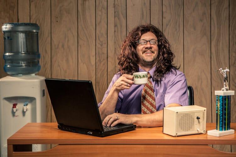 Mann mit Kaffee vor Laptop im 70er-Jahre Look