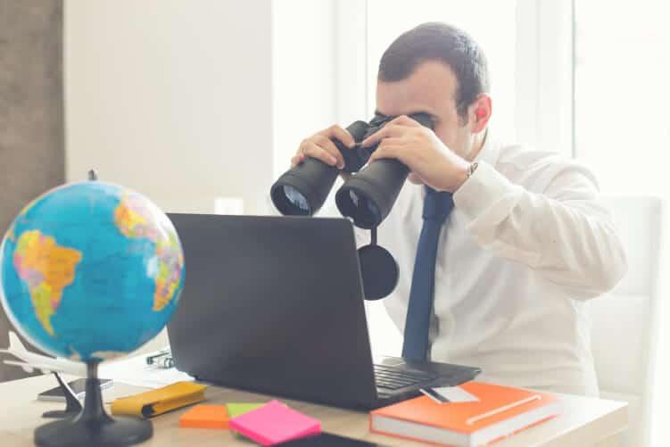 Nach dem richtigen Interviewpartner suchen - Mann mit Fernglas vor PC