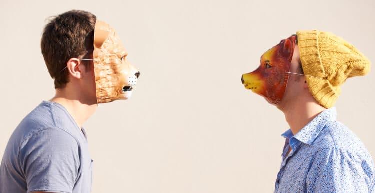 zwei Männer mit Tiermasken setehen sich gegenüber