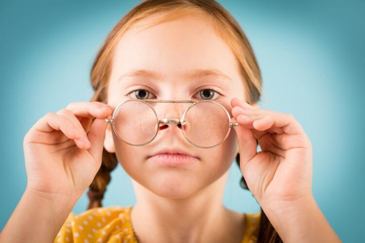 kleines Mädchen setzt sich eine Brille auf die Nase