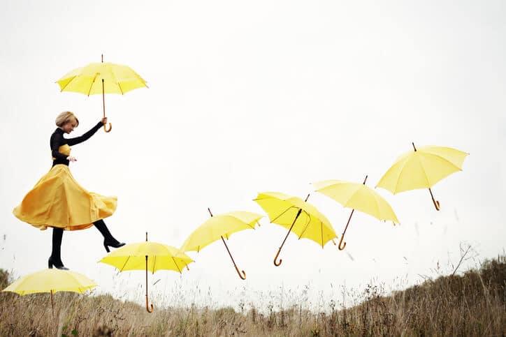 Frau mit gelben Regenschirmen
