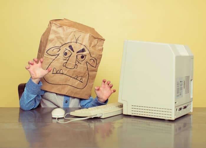 Kind mit Papiertüte über dem Kopf auf dem ein Monster ist, vor einem Computer.