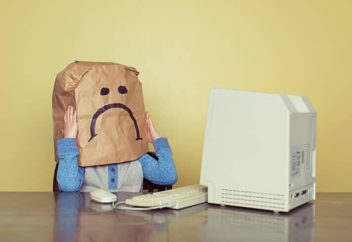 : Kind mit Papiertüte auf dem ein trauriges Smiley ist vor Computer