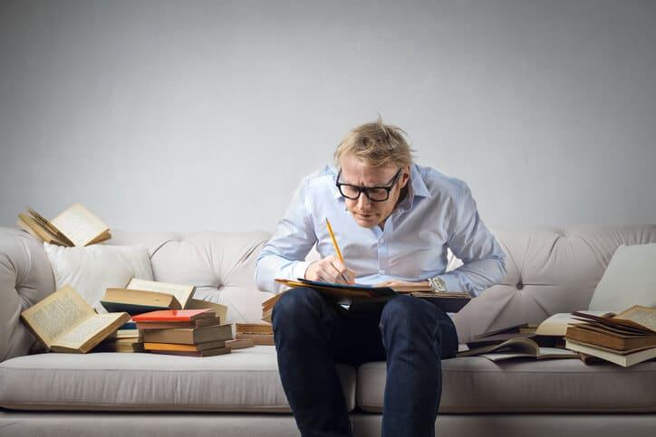 Mann mit Büchern beim Schreiben