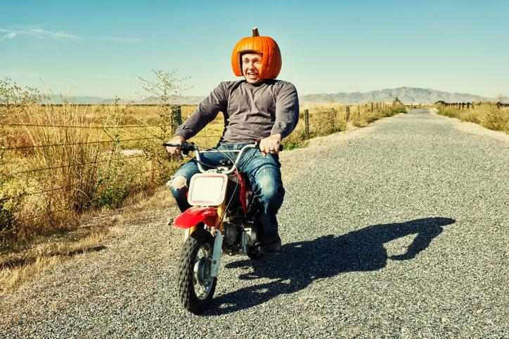 Mann mit Kürbis-Helm auf Motorrad.
