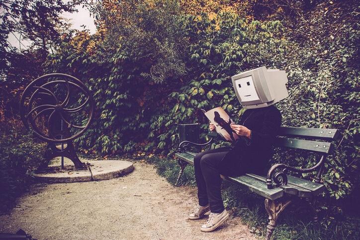 Person mit PC-Kopf auf Parkbank