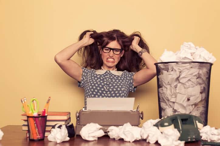 Frau mit Schreibblockade vor Schreibmaschine
