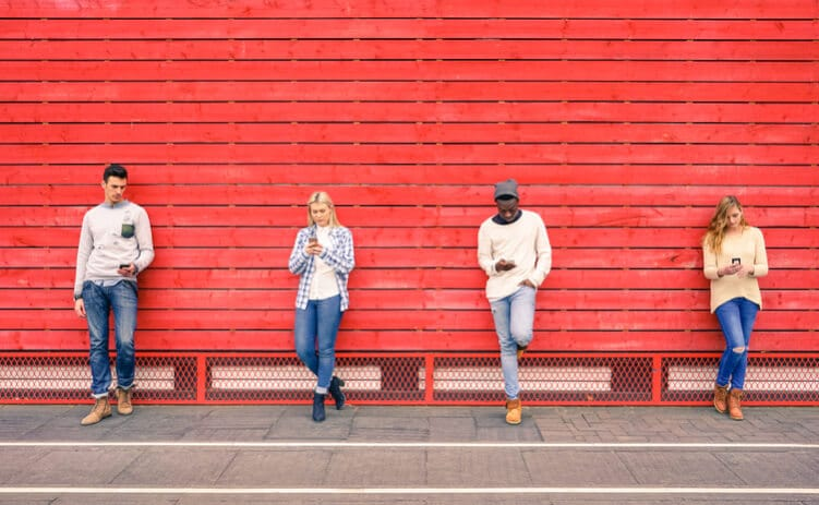 vier junge Leute nutzen Smartphones