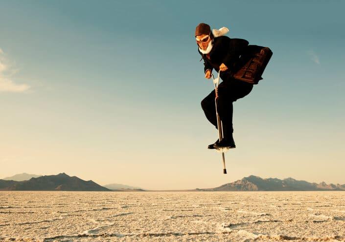 Mann auf Sprungfeder in der Wüste
