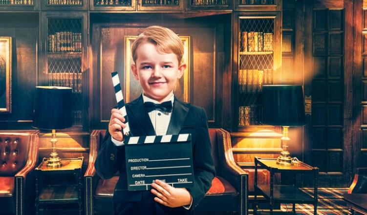 junge-in-smoking-hält-filmklappe