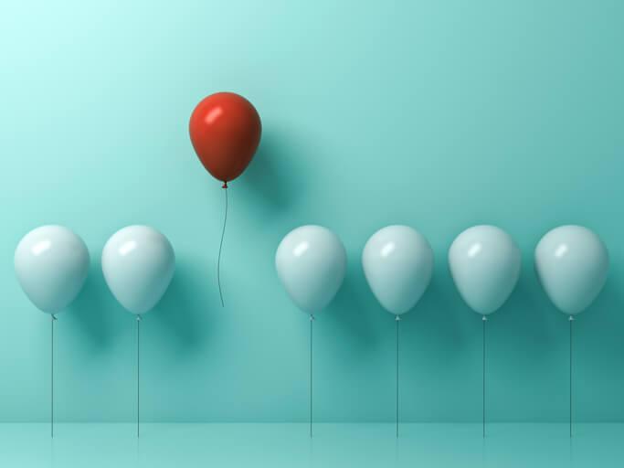 roter-luftballon-hebt-sich-ab-vo-von-mint-grünem-hintergrund