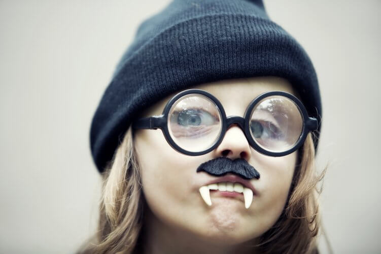 Kind mit Vampirzaehnen, brille und muetze