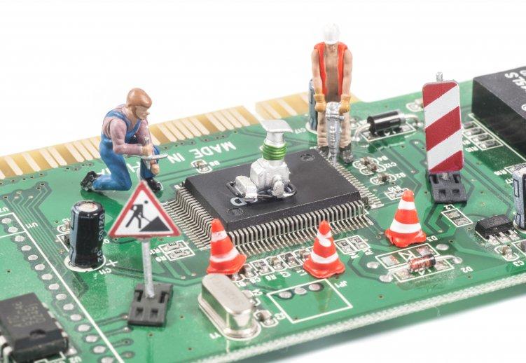 Bild einer Computerplatine, auf der Spielzeug-Bauarbeiter aufgestellt sind